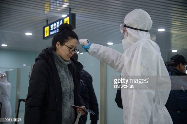 Woman has her temperature taken as foreign diplomats and embassy staff prepare to board a flight to Vladivostok at Pyongyang International Airport on...