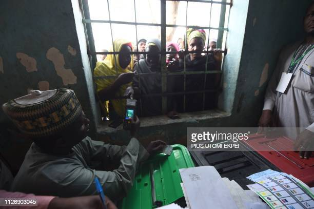 A woman has her thumb print verified through the window to vote at a polling station in Kano commercial capital of northern Nigeria on February 23...