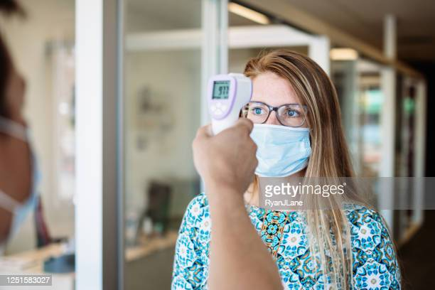 woman has temperature taken by office worker wearing mask - fever stock pictures, royalty-free photos & images