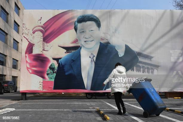 A woman hauls a wheelie bin past a faded propaganda billboard featuring an image of China's President Xi Jinping in a car park in Beijing on March 19...