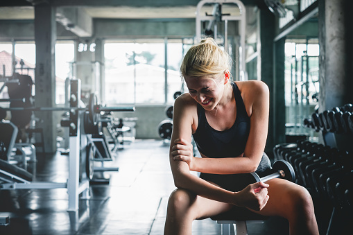 Woman have accident injury and hurt at arms while workout and weight training at gym, muscle pain concept 1008885346