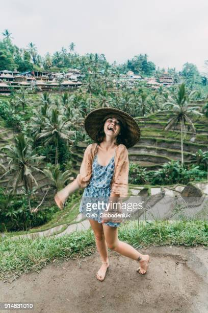 Woman have fun on Tegallalang rice field in Bali, Indonesia in asian style conical hat