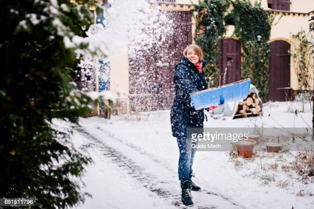 woman havin fun while shoveling snow. - snow shovel stock photos and pictures