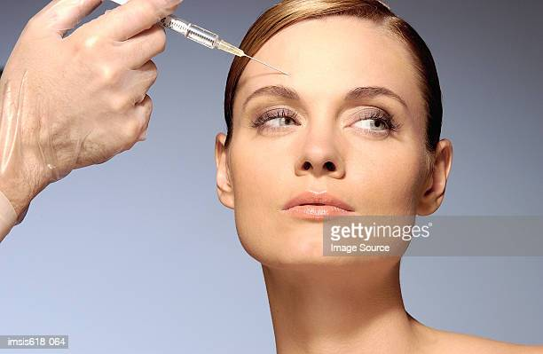 woman having a botox injection - botox stock pictures, royalty-free photos & images
