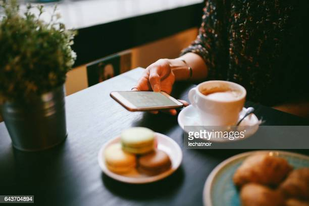 Woman having a coffee and sweets in the cafe