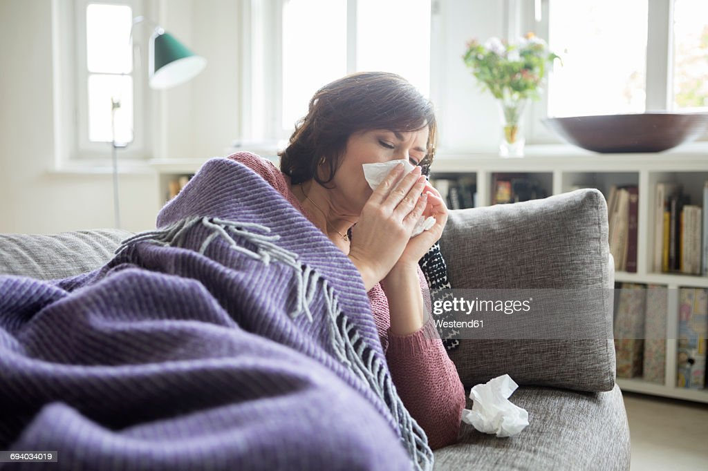 Woman having a cold lying on the sofa : Stock Photo