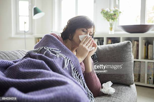 woman having a cold lying on the sofa - resfriado y gripe fotografías e imágenes de stock