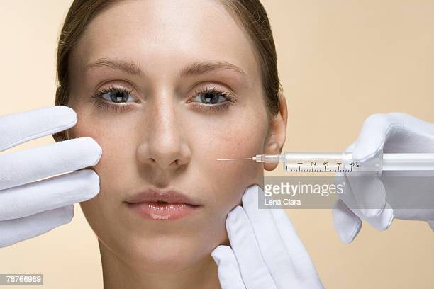 a woman having a collagen injection - beige glove stock photos and pictures
