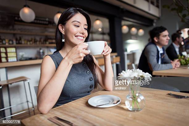 woman having a cup of coffee at a restaurant - koffie drank stockfoto's en -beelden