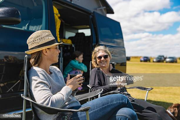 woman having a cuppa by the camper van with her mother and daughter - vacations stock pictures, royalty-free photos & images
