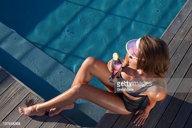 Mujer disfruta de una bebida junto a la piscina