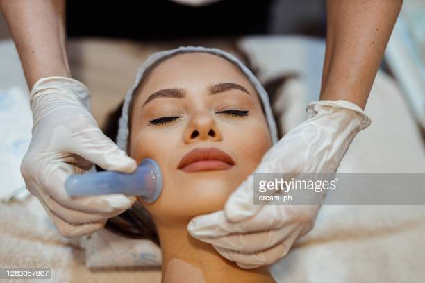 woman having a facial cupping treatment in the beauty clinic - hands cupped stock pictures, royalty-free photos & images