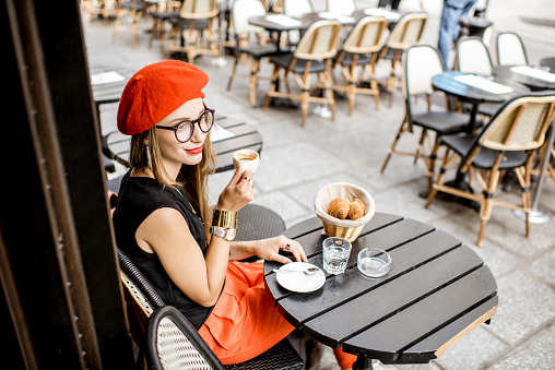 Woman having a french breakfast at the cafe 835925820