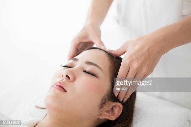 Woman having a head massage at a salon