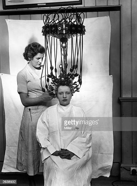 A woman having a perm using a new perming machine made by Messrs Gallia The machine works on ordinary mains electricity converted to 4 volts It has...