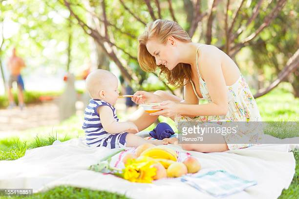 A woman having a picnic with a baby in the park