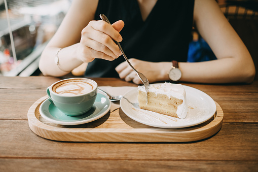 Woman having a relax time eating a slice of cake and having coffee in cafe - gettyimageskorea
