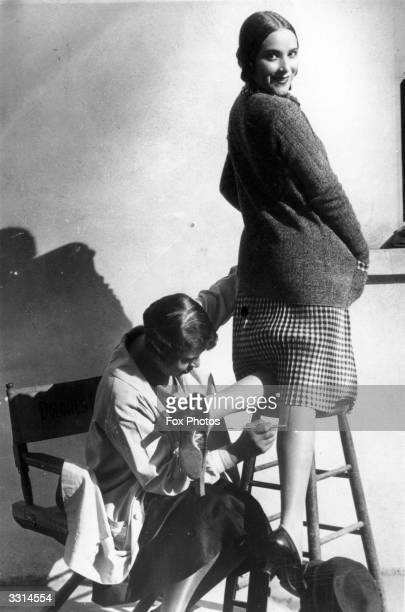 A woman having a seam painted onto her leg to make it appear that she is wearing stockings