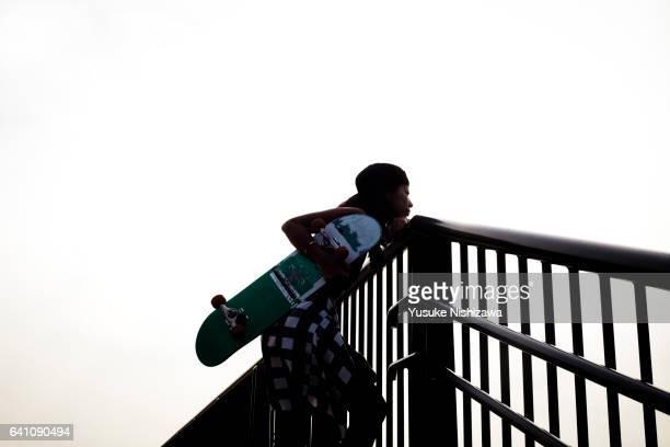 woman having a skateboard - yusuke nishizawa stock-fotos und bilder