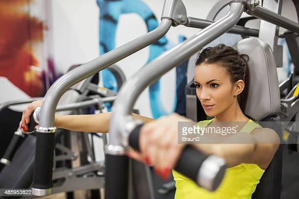 Woman having a sports training on exercise machine at gym.