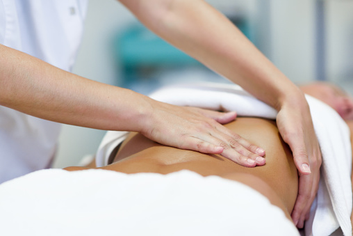 Woman having abdomen massage by professional osteopathy therapist 983169046