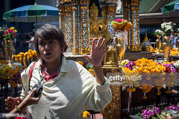 Woman having an interview for the media with the Erawan statue in the back side, at the reopened Erawan Shrine in Central Bangkok on August 19th...