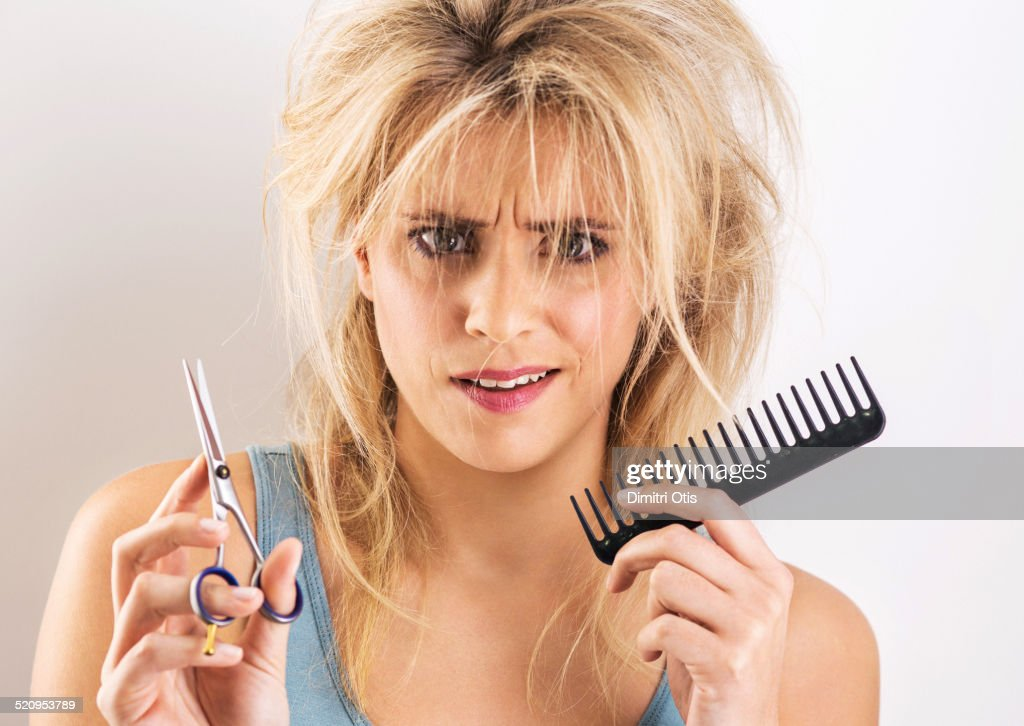 Woman having bad hair day with scissors and comb : Stock Photo