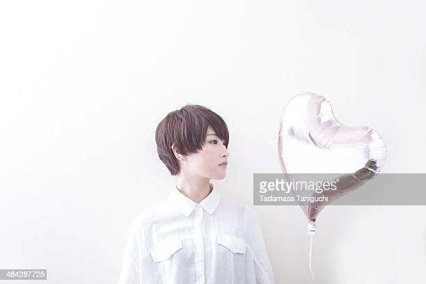 woman having balloon of heart shape - ショートヘア ストックフォトと画像