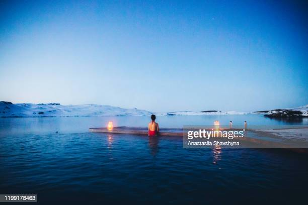 woman having bath in thermal pool with view of the snowy mountains and frozen lake in iceland - sport venue stock pictures, royalty-free photos & images