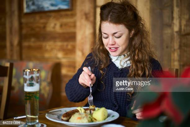 woman having beer, sausages, sauerkraut and potatoes in a wooden mountain lodge