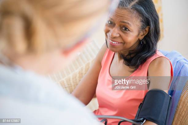 Woman having blood pressure taken on sofa