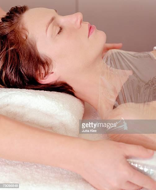 Woman having body mask at beauty spa