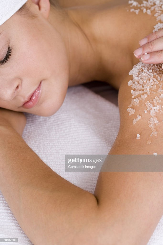 Woman having body scrub rubbed on her back : Stockfoto