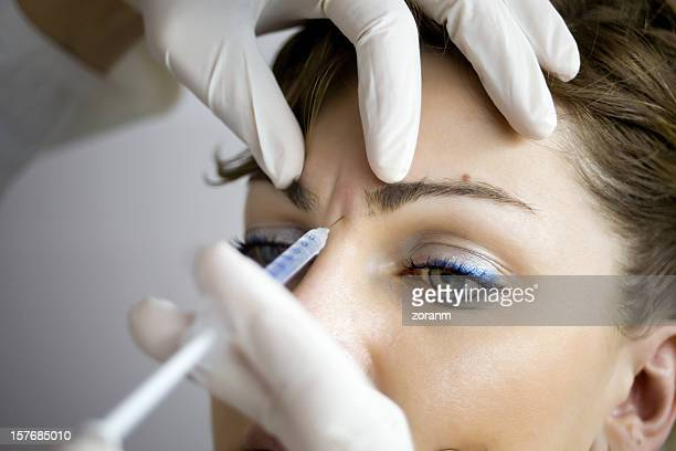 a woman having botox injections - botox stock pictures, royalty-free photos & images
