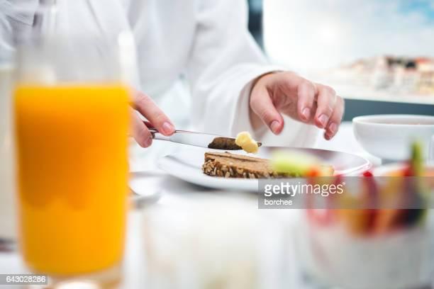 Frau mit Frühstück im Hotelzimmer
