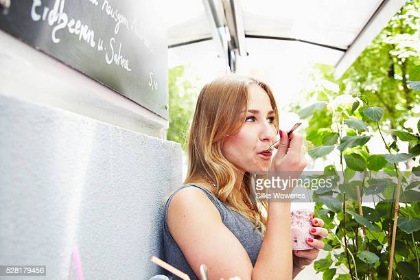 Woman having breakfast in small cafe on sunny day
