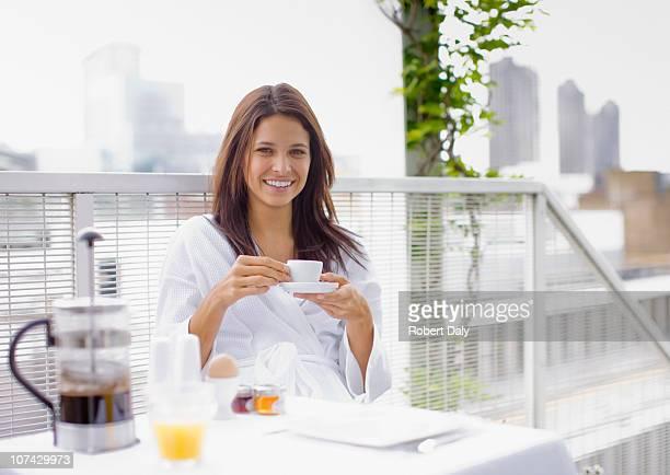 Frau mit Frühstück auf dem Balkon
