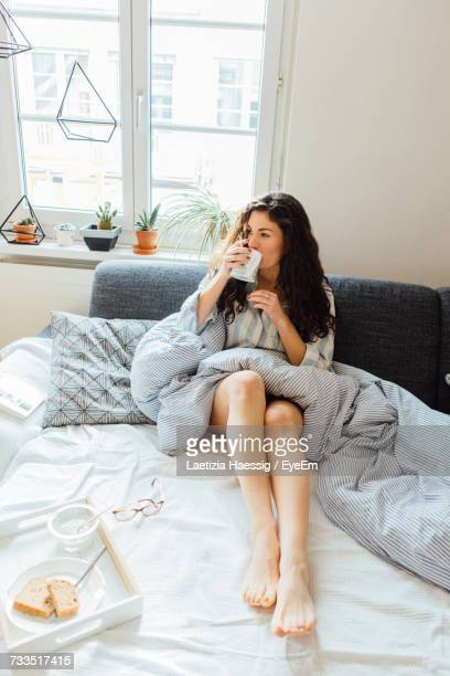 woman having breakfast on bed at home - breakfast in bed stock pictures, royalty-free photos & images