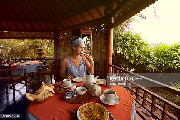 Woman having breakfast on hotel terrace, Bali, Indonesia