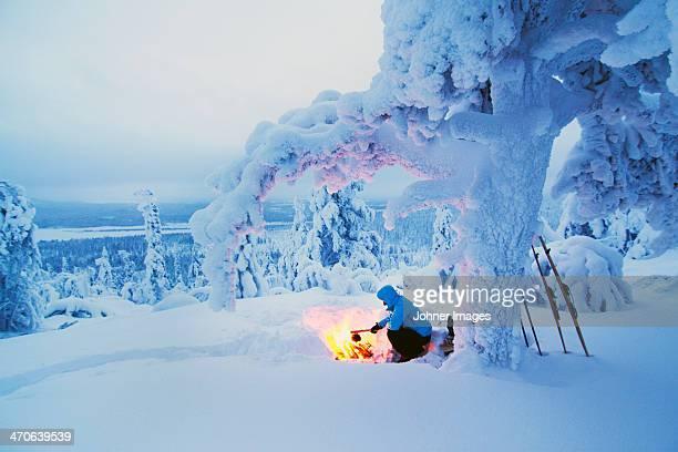 Woman having campfire at winter