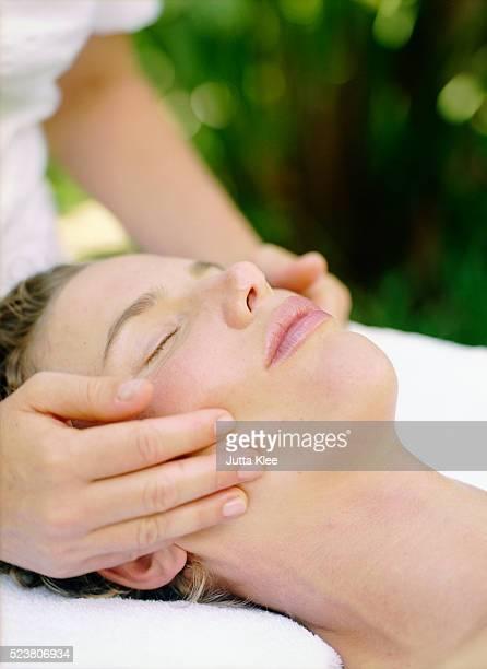 woman having cheeks massaged - massaggio sensuale foto e immagini stock