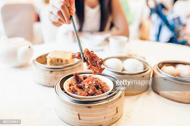 Woman having Chicken's Feet and other dim sum