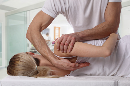 Woman having chiropractic back adjustment. Osteopathy, Alternative medicine, pain relief concept. Physiotherapy, sport injury rehabilitation 645777264