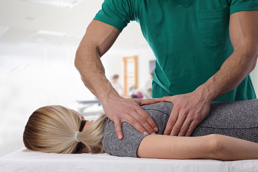 Woman having chiropractic back adjustment. Osteopathy, Alternative medicine, pain relief concept. Physiotherapy, sport injury rehabilitation 645787394