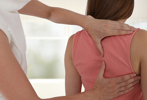 Woman having chiropractic back adjustment. Osteopathy, Physiotherapy, sport injury rehabilitation concept 987812234