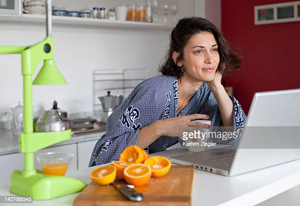 woman having coffee and juice, laptop on the table