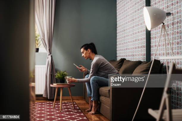 Woman having coffee and reading news feed on smart phone