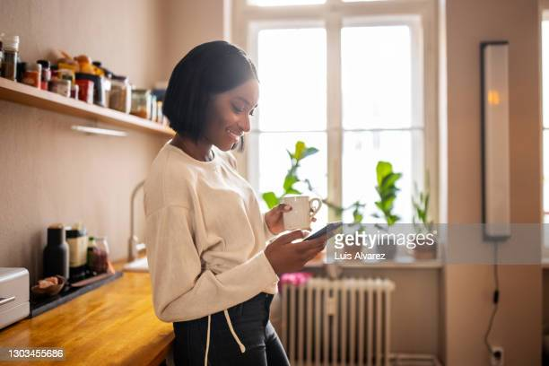woman having coffee and texting on her phone at home - covid-19 stock pictures, royalty-free photos & images