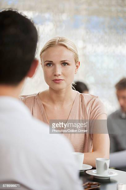 Woman having coffee in cafe with man