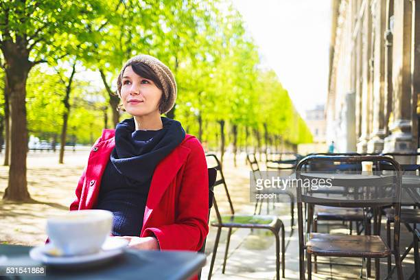 Woman having coffee in parisian cafe in park.